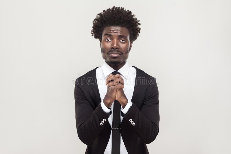O homem de negócios africano que olha a câmera e desculpa-se imagem de stock royalty free