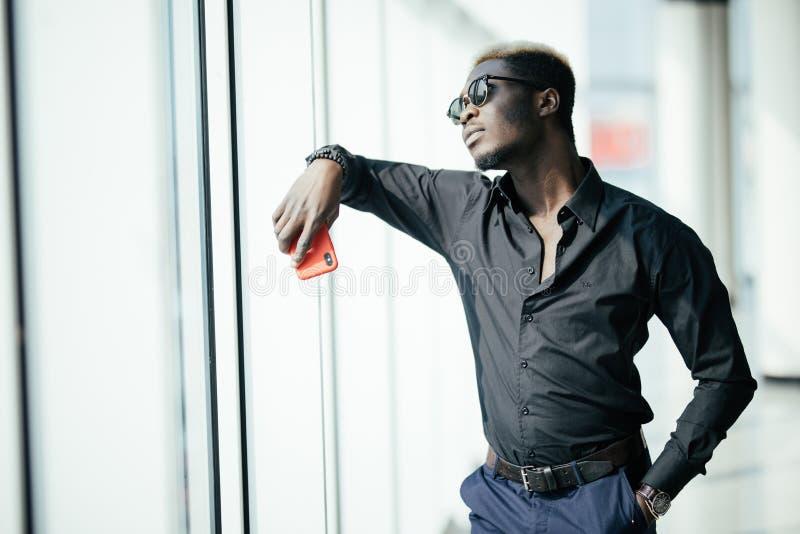 O homem de negócios afro-americano considerável na roupa ocasional e nos monóculos está mantendo o telefone celular contra janela imagem de stock royalty free