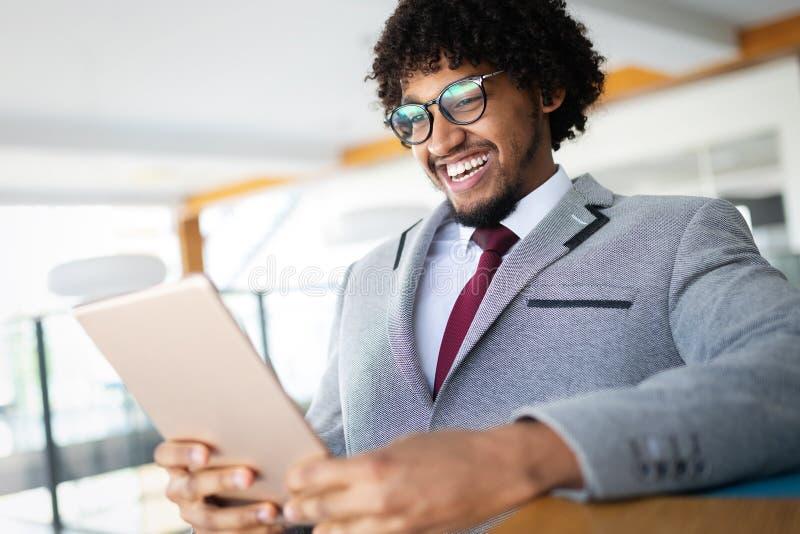 O homem de negócios afro-americano considerável no terno clássico está usando uma tabuleta digital fotografia de stock royalty free