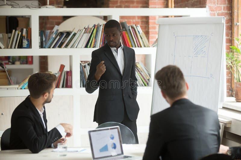 O homem de negócios afro-americano dá a apresentação ao trabalho dos sócios fotos de stock royalty free