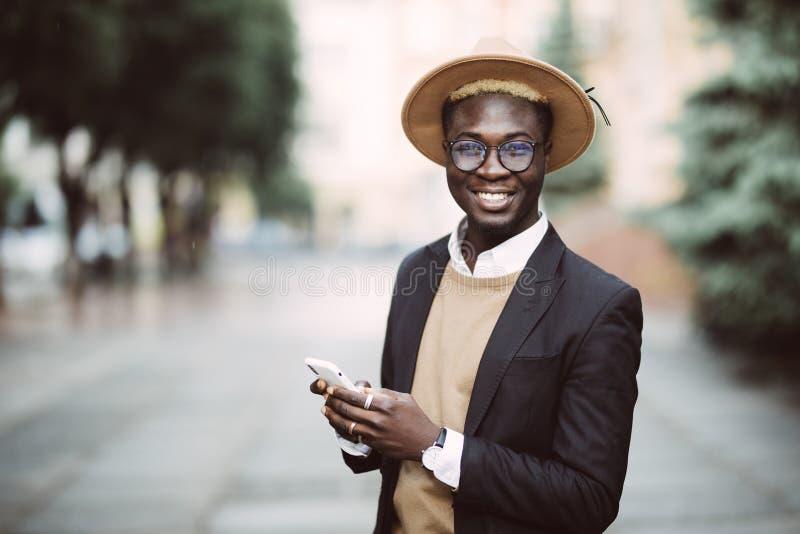 O homem de negócios afro-americano novo considerável nos vidros e no chapéu está usando o smartphone e o sorriso, estando na cida imagem de stock