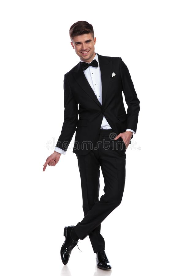 O homem de negócios alegre relaxado está de pernas cruzadas e pontos para tomar partido imagens de stock royalty free