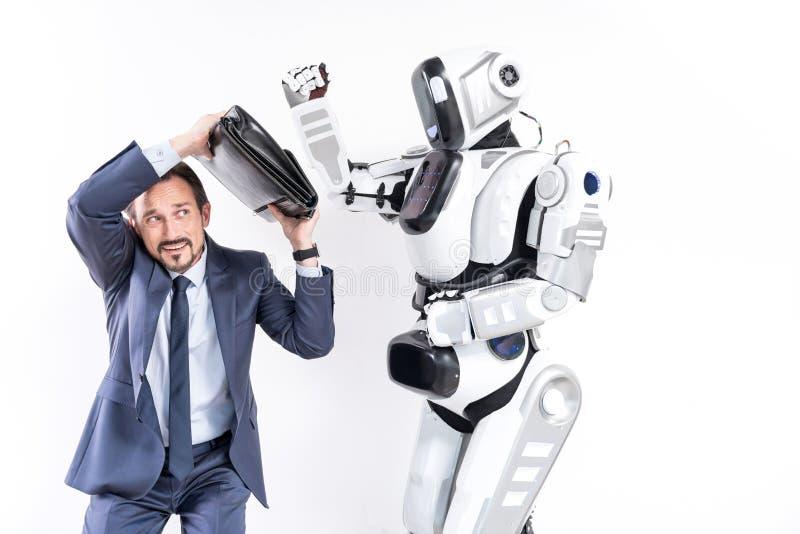 O homem de negócios amedrontado adulto está escapando do robô de ataque foto de stock royalty free