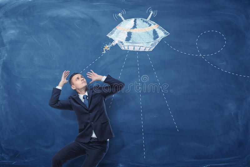 O homem de negócios amedrontou pelos pires de voo pintados no quadro-negro azul atrás dele fotos de stock