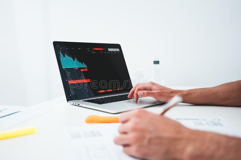 O homem de negócios analisa relatórios digitais no monitor e em preparar da tela o relatório financeiro para acionistas imagem de stock