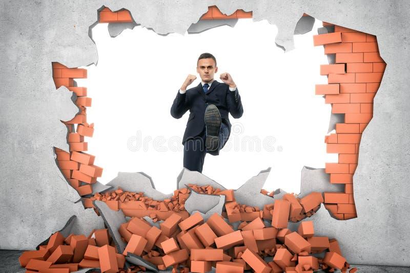 O homem de negócios arruina a parede de tijolo com seu pé no fundo branco fotografia de stock