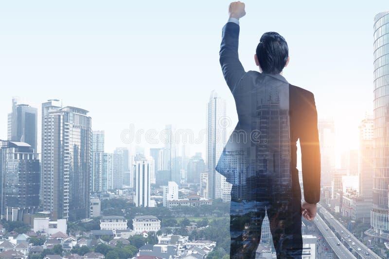 O homem de negócios asiático bem sucedido aumentou o braço para o céu fotos de stock royalty free