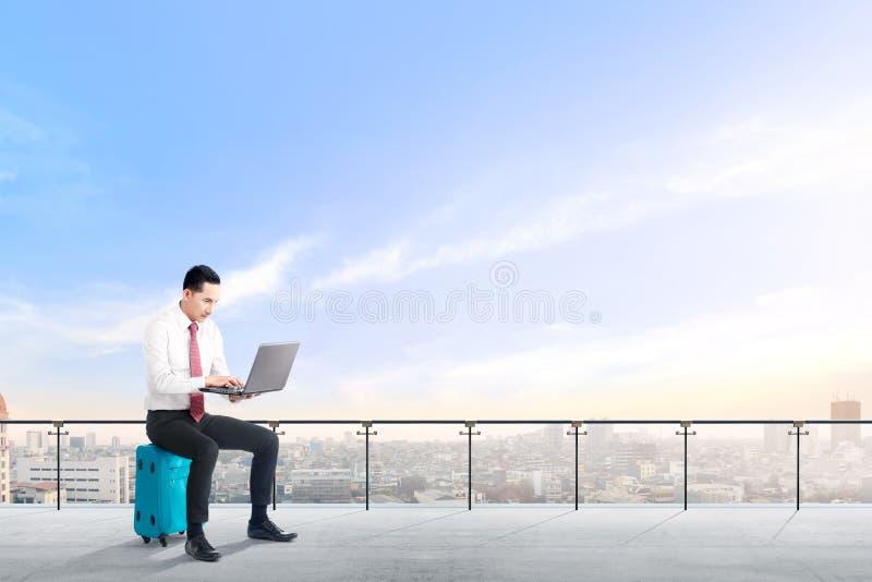 O homem de negócios asiático considerável que senta-se na mala de viagem azul guarda o portátil e o trabalho no terraço moderno imagens de stock royalty free