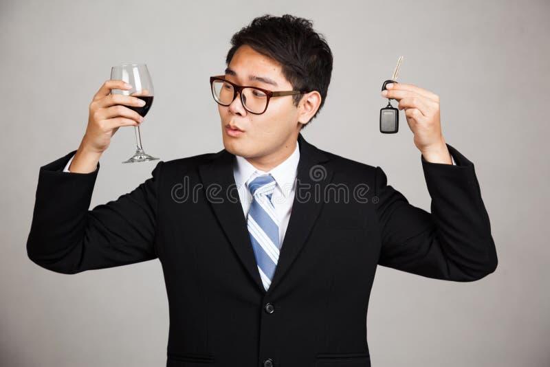 O homem de negócios asiático escolhe a bebida ou condu-la fotografia de stock
