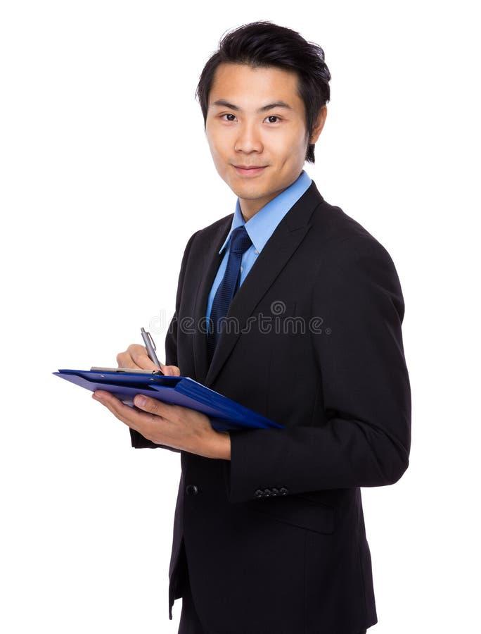 O homem de negócios asiático escreve na prancheta fotografia de stock royalty free