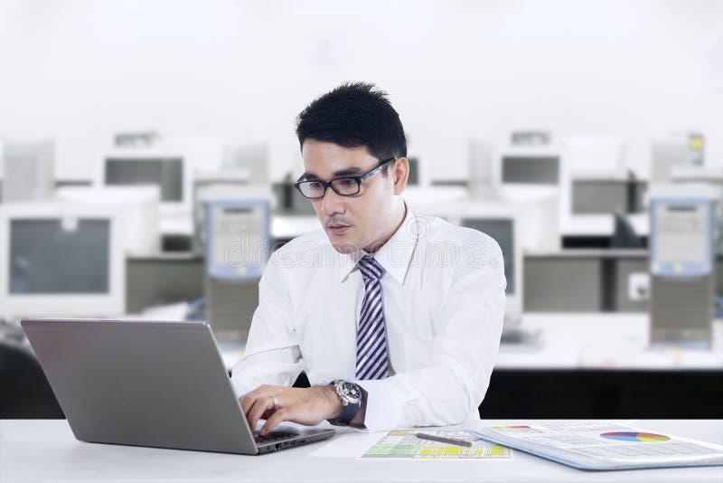 O homem de negócios asiático está trabalhando no escritório fotos de stock royalty free