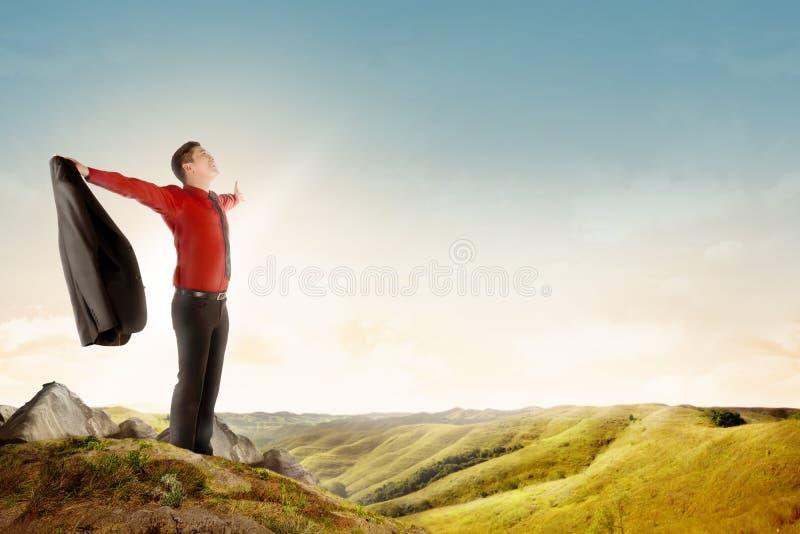 O homem de negócios asiático feliz que guarda uma posição do terno sobre a montanha comemora seu bem sucedido fotos de stock royalty free