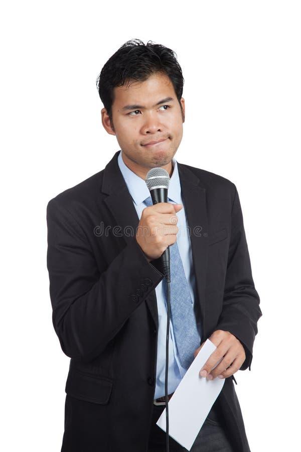 O homem de negócios asiático hesita falar com o papel foto de stock
