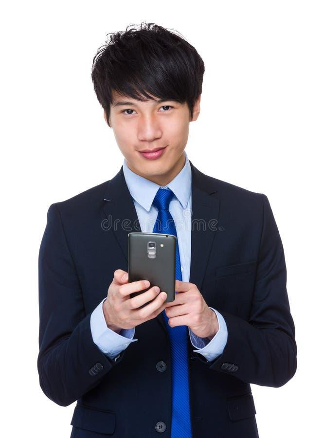 O homem de negócios asiático novo envia uma mensagem de texto foto de stock royalty free