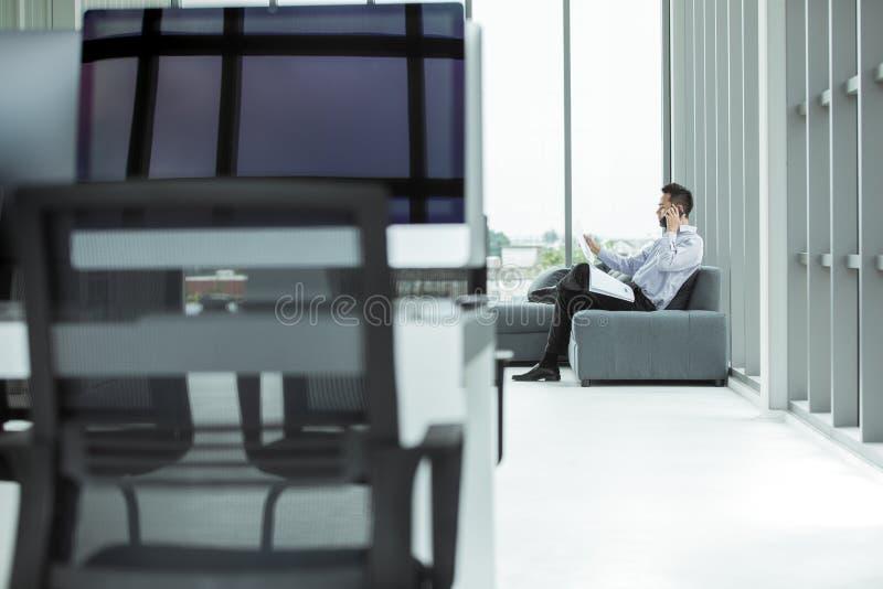 O homem de negócios asiático novo que usa o smartphone no sofá lá é docum fotos de stock