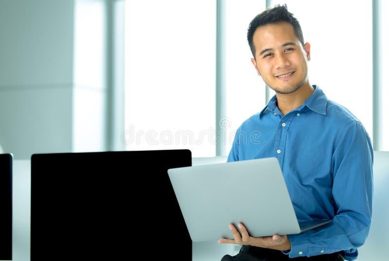 O homem de negócios asiático novo sorri com sucesso na sagacidade moderna do escritório fotos de stock royalty free