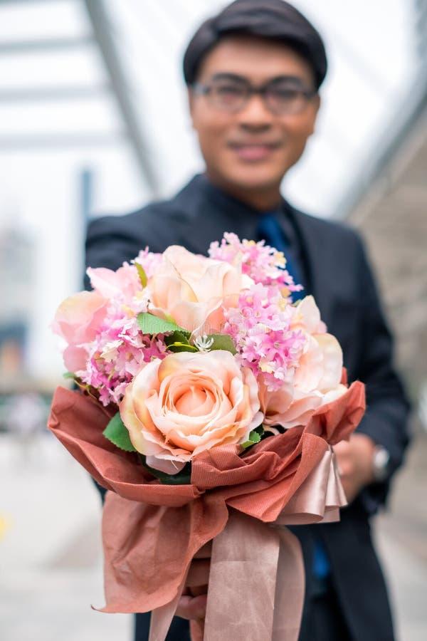 O homem de negócios asiático que guarda o ramalhete das rosas para felicita fotografia de stock