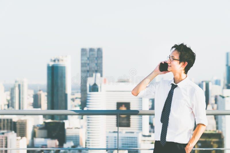O homem de negócios asiático que usa o telefone celular chama o telhado da construção, copia o espaço no fundo da opinião da cida fotografia de stock royalty free