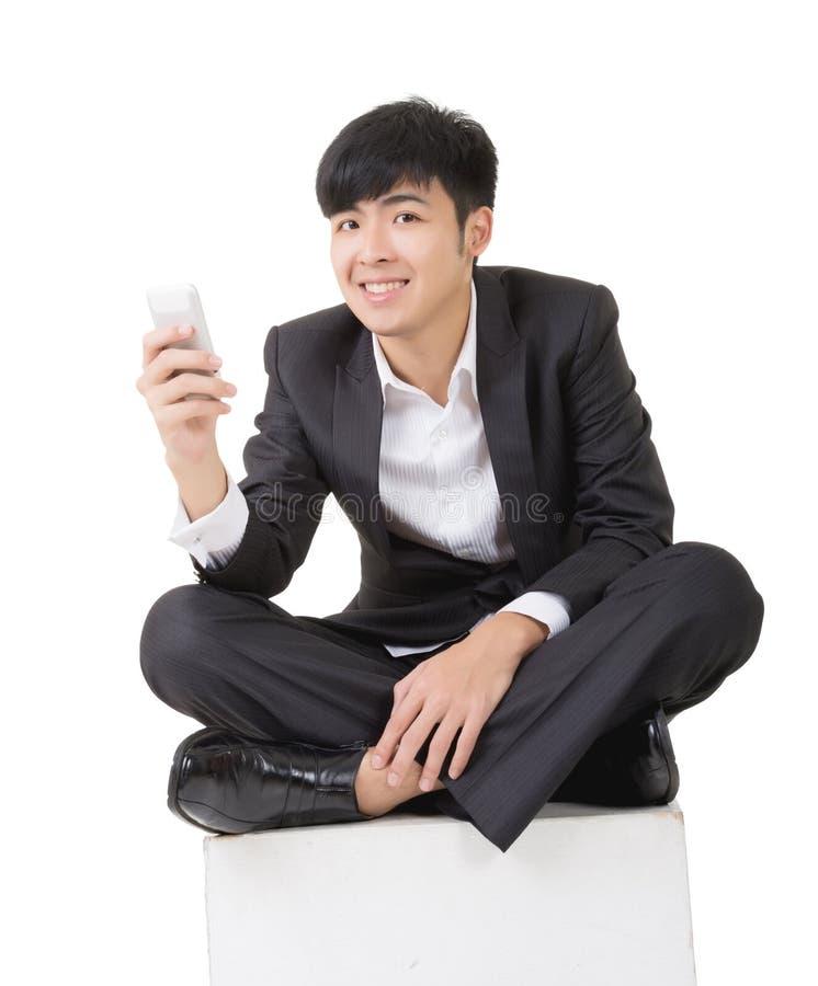 O homem de negócios asiático senta e usa o telefone esperto fotografia de stock