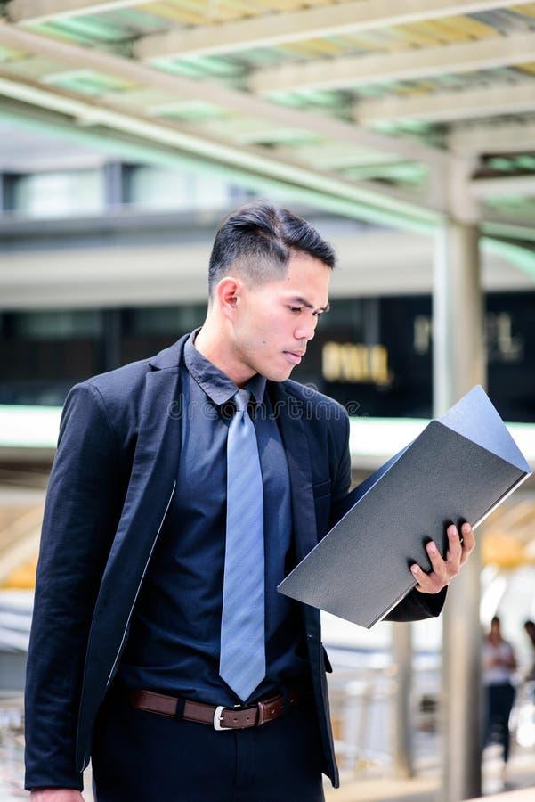 O homem de negócios asiático tem guardar um dobrador do documento e uns vagabundos pretos fotografia de stock royalty free