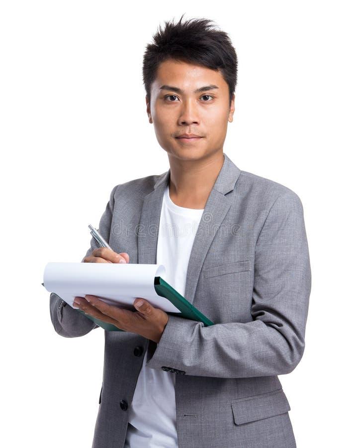 O homem de negócios asiático toma a nota na prancheta foto de stock