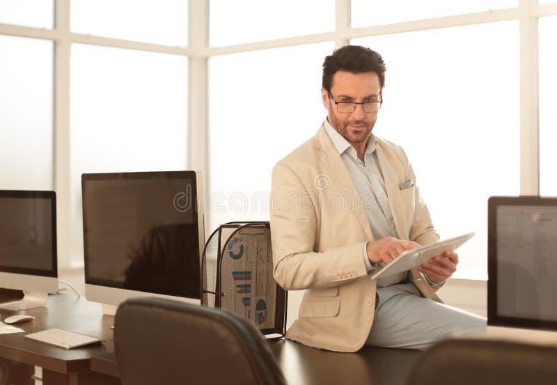 O homem de negócios atento usa uma tabuleta digital em um escritório moderno imagens de stock royalty free