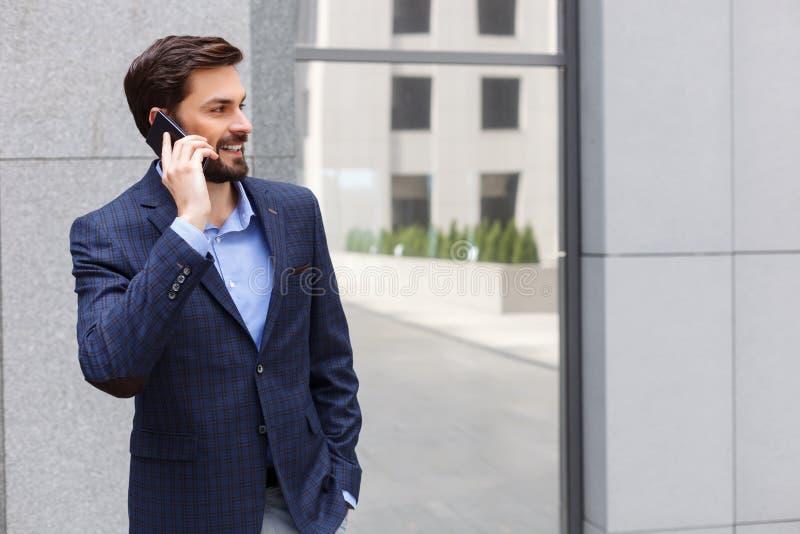 O homem de negócios atrativo está comunicando-se no telefone imagem de stock royalty free