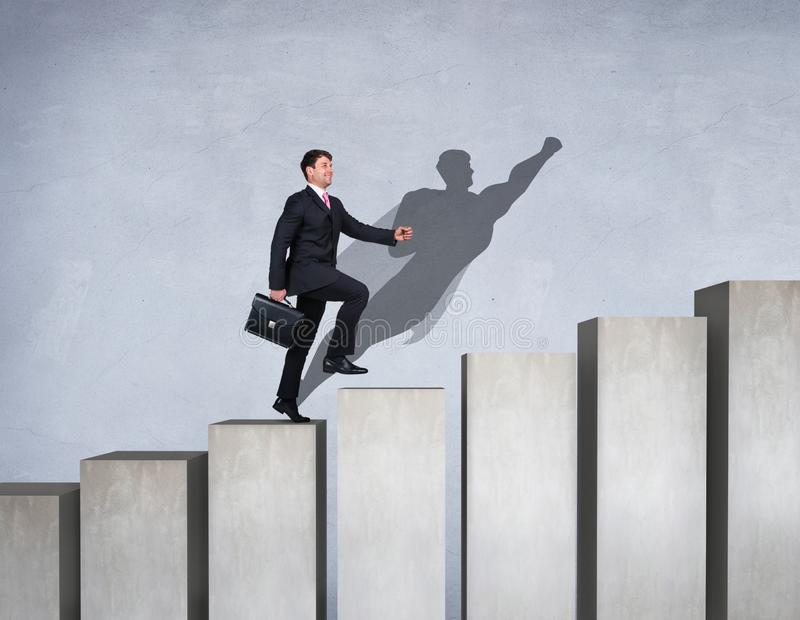 O homem de negócios aumenta acima na escada da carreira com sombra do super-herói na parede foto de stock