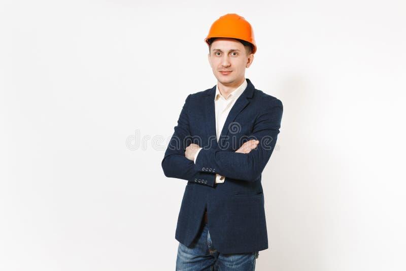 O homem de negócios bem sucedido considerável novo no terno escuro, capacete alaranjado da construção protetora que guarda as mão imagem de stock royalty free