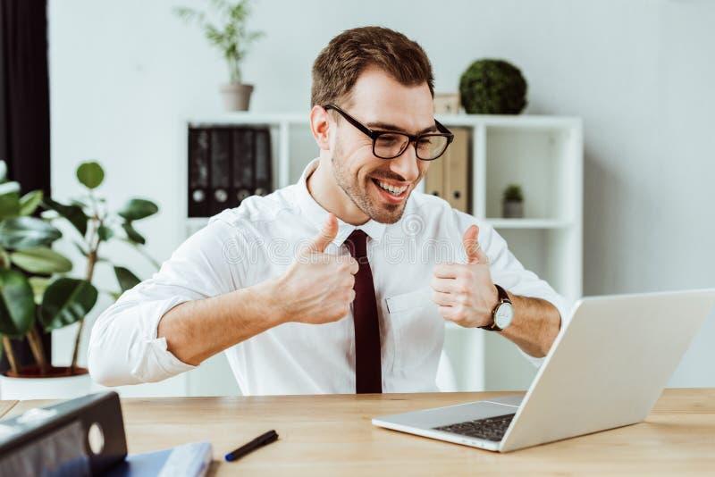 o homem de negócios bem sucedido considerável que faz o vídeo chama o portátil e mostrar imagem de stock