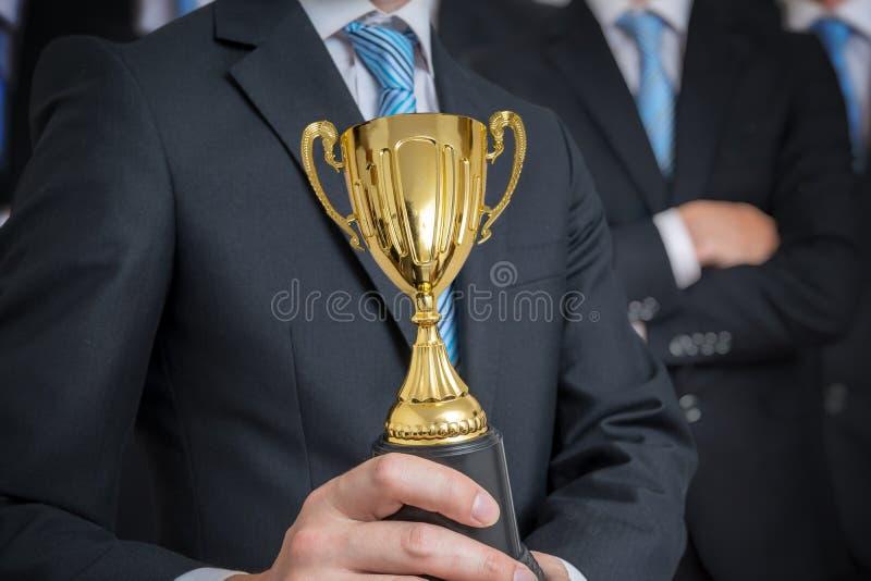 O homem de negócios bem sucedido foi concedido com o troféu para habilidades excelentes foto de stock royalty free