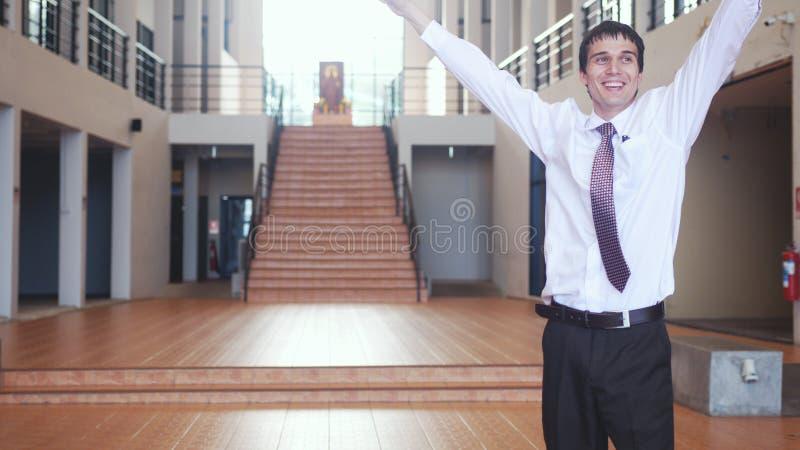O homem de negócios bem sucedido novo feliz está com levantar as mãos da alegria no escritório moderno Conceito do negócio, econo fotografia de stock