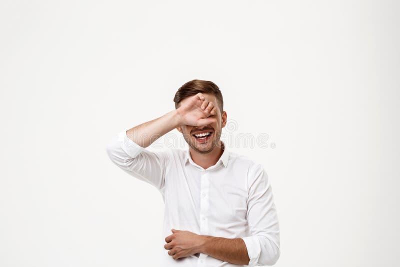O homem de negócios bem sucedido que ri, escondendo eyes cede atrás o fundo branco fotografia de stock