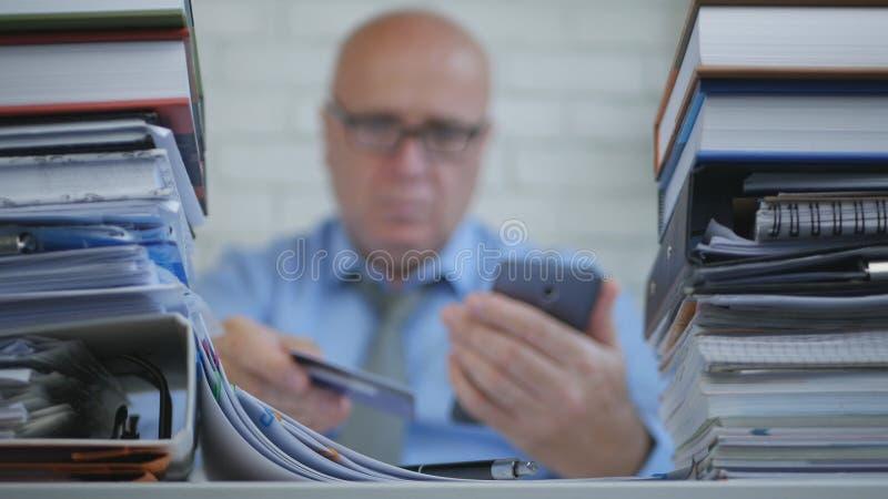 O homem de negócios In Blurred Image faz pagamentos em linha com Smartphone e o cartão de banco imagem de stock royalty free
