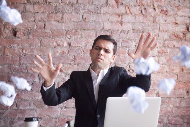 O homem de negócios cansado irritado para o trabalho, joga o papel amarrotado imagem de stock