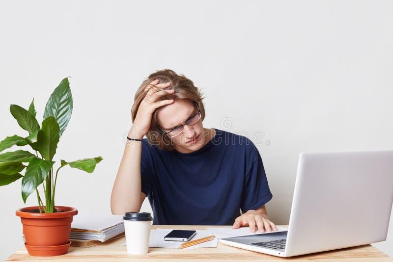 O homem de negócios cansado tem o olhar da dor de cabeça exasperately nos originais, trabalho o dia inteiro no relatório financei imagem de stock