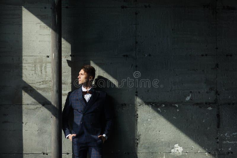 O homem de negócios caucasiano considerável vestiu-se no terno perto da janela no estúdio do interior do sótão imagens de stock