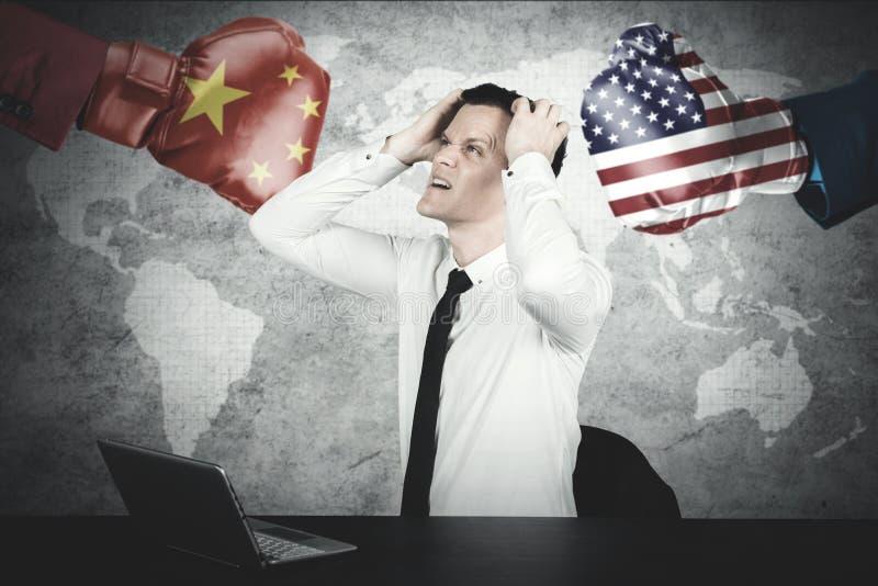 O homem de negócios caucasiano olha deprimido com guerra comercial imagens de stock royalty free