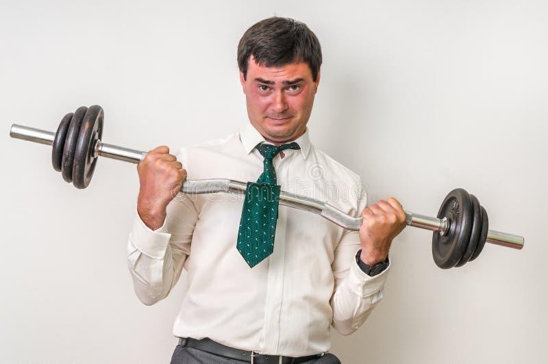 O homem de negócios com barbell está levantando o peso pesado imagens de stock royalty free