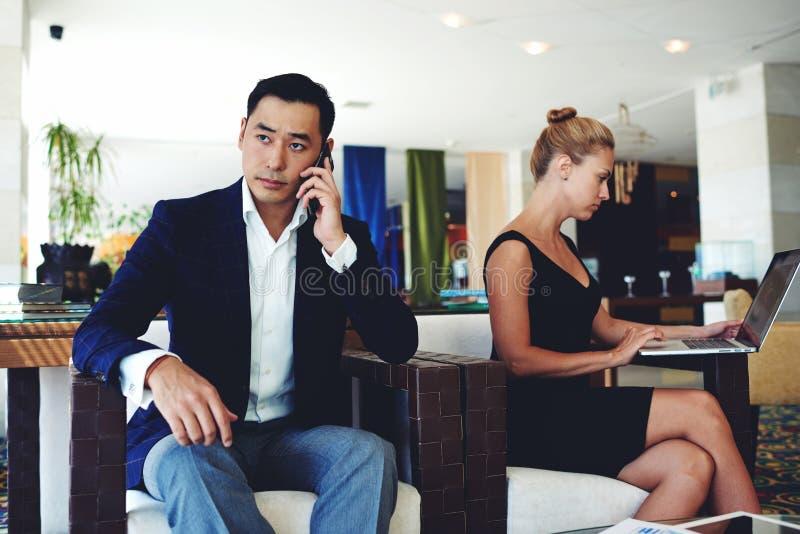 O homem de negócios com cara séria que discute o trabalho emite pelo telefone celular, mulher esperta nova que trabalha no laptop imagens de stock