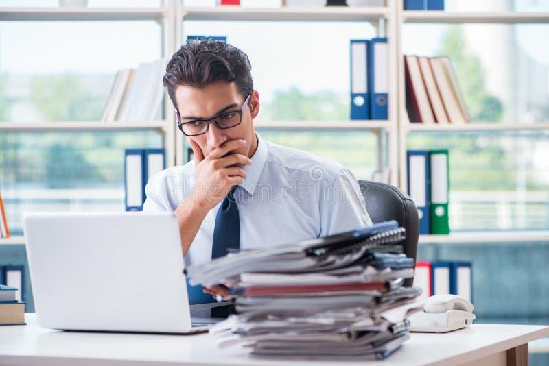 O homem de negócios com o documento excessivo do trabalho que trabalha no escritório fotografia de stock royalty free