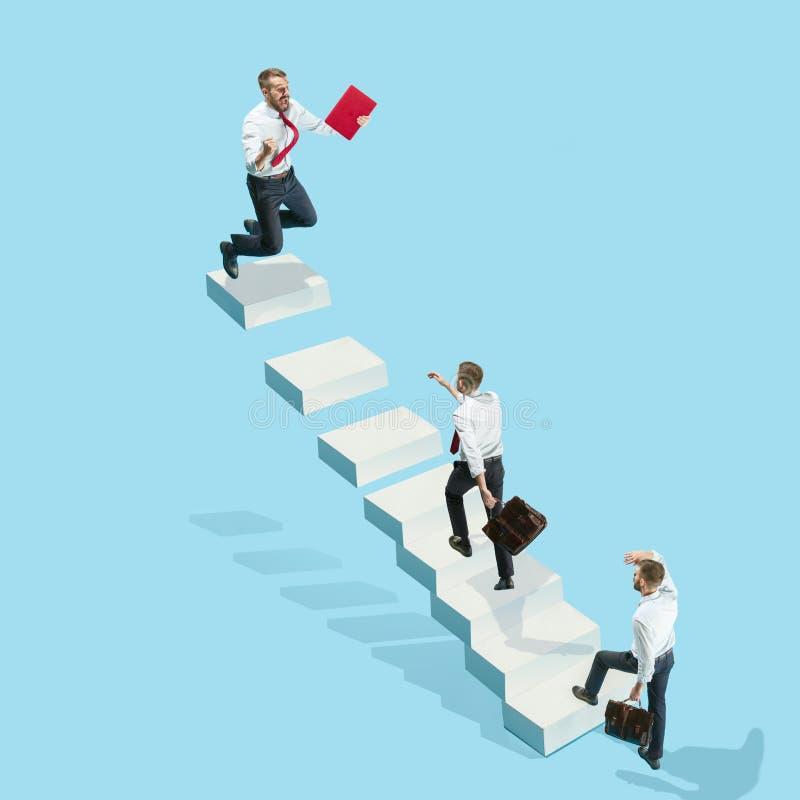 O homem de negócios com pasta à disposicão, funcionamentos levanta a escada da carreira Isolado no fundo branco imagem de stock royalty free