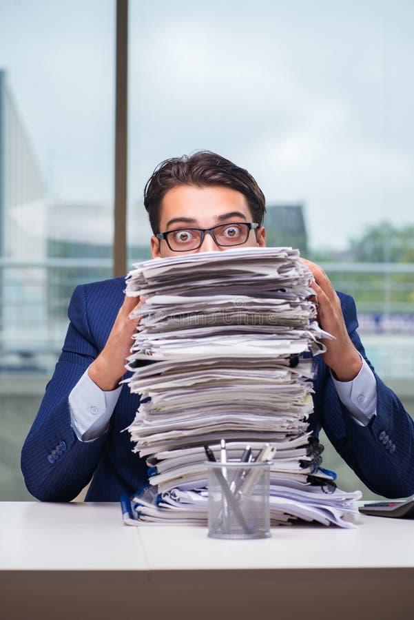 O homem de negócios com a pilha da pilha do documento de papel no escritório imagem de stock royalty free