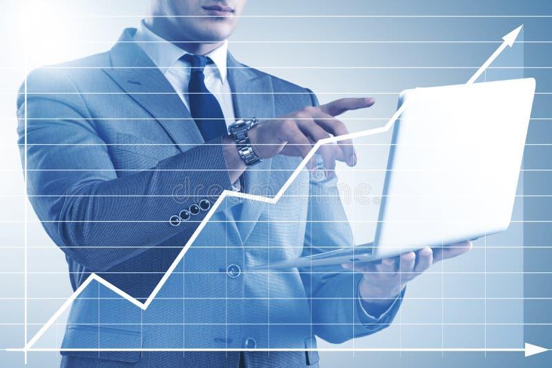 O homem de negócios com o portátil no conceito da finança e da operação bancária foto de stock royalty free