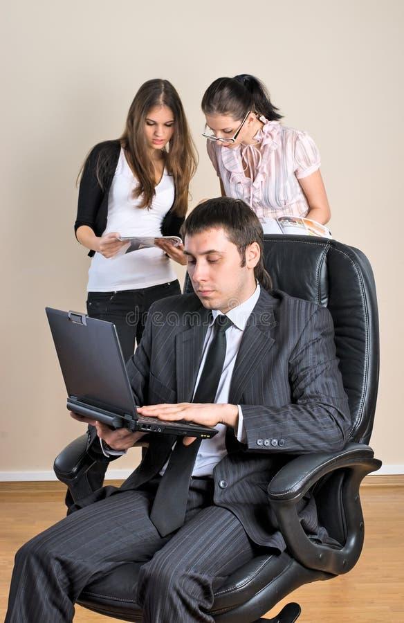 O homem de negócios com portátil trabalha no escritório imagem de stock