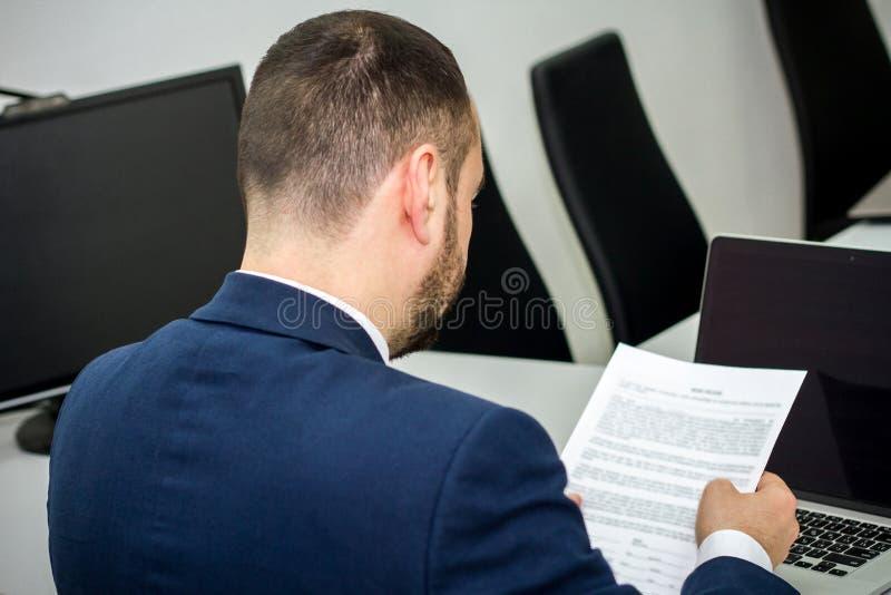 O homem de negócios com uma barba lê um contrato antes de assinar em um la fotografia de stock royalty free