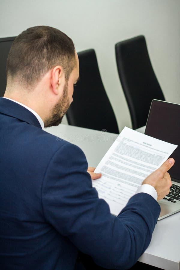 O homem de negócios com uma barba lê um contrato antes de assinar em um la fotos de stock