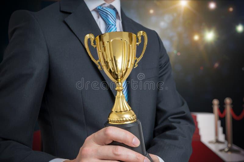 O homem de negócios concedido bem sucedido está guardando o troféu dourado Luzes e flashes no fundo fotos de stock
