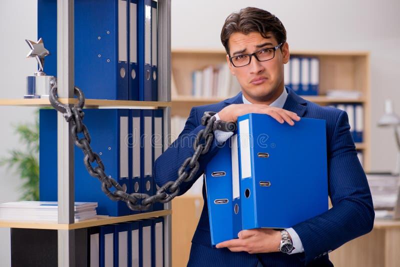 O homem de negócios considerável acorrentado à prateleira do escritório imagem de stock