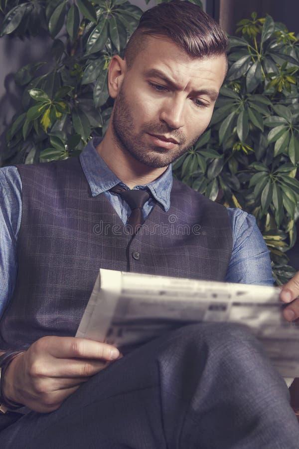 O homem de negócios considerável brutal elegante à moda senta-se na cadeira e lê-se a notícia no jornal Retrato do homem no terno foto de stock royalty free